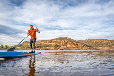 horsetooth reservoir: A senior male paddling on a stand up paddleboard on a calm mountain lake - Horsetooth Reservoir near Fort Collins, Colorado, fall scenery