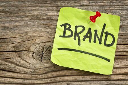 브랜드 알리미 - 나뭇결 치 고 매듭 된 목재 보드에 대한 녹색 스티커 메모에 필기 스톡 콘텐츠