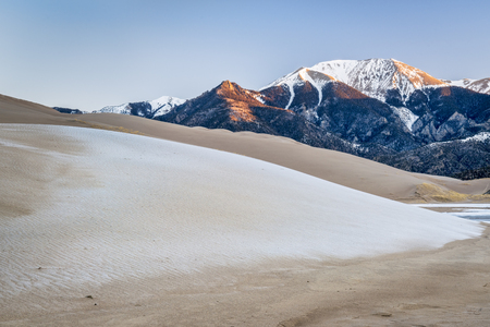 winter dawn over sand dunes covered by frost and first light on Sangre de Cristo Mountains - Great Sand Dunes National Park, Colorado