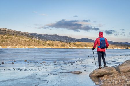 horsetooth reservoir: male hiker at a shore of frozen Horsetooth Reservoir near Fort Collins, Colorado - winter hiking concept