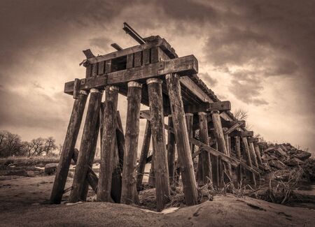 railroad timber trestle destroyed by river flooding - St Vrain Creek near Platteville, Colorado, sepia toning Stock Photo
