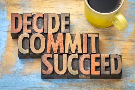 commit: Decide, commit, succeed word abstract in vintage letterpress wood type with a cup of coffee