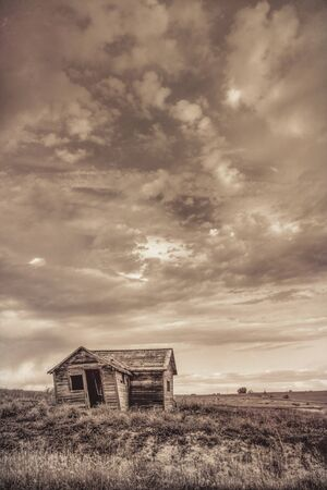 old abandoned farm house on Colorado prairie with stormy sky, sepia toning