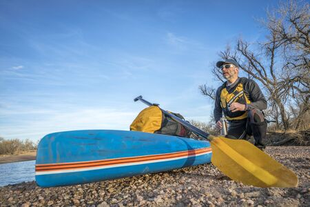 a senior male paddler is taking a rest and tea break on a gravelbar during stand up paddling on the South Platte RIver, cold season scenery Stock Photo