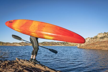 portaging and launching kayak on lake shore, Horsetooth REservoir, Colorado Stock Photo