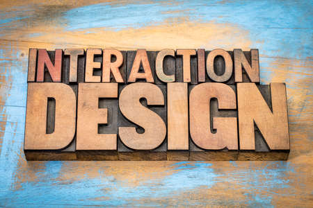 letterpress type: interaction design - designing interactive digital products, environments, systems, and services - word abstract in vintage letterpress wood type against grunge wooden background Stock Photo