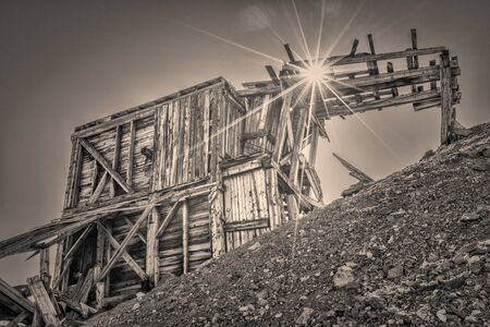 ruins of gold mine near Mosquito Pass in Rocky Mountains, Colorado - upper station of aerial tramway used to transport gold ore, retro sepia toning with a film grain