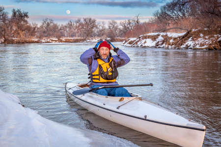 scared or concerned senior canoe paddler during winter expedition on the South Platte River in Colorado photo