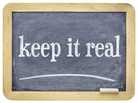 Keep it real text on a slate blackboard with chalk isolated with a clipping path