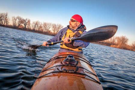 mature male paddler exercising (turning boat using rudder stroke with his wing carbon fiber paddle) in a home built wooden sea kayak on lake, fall scenery  in Colorado, view from kayak bow photo