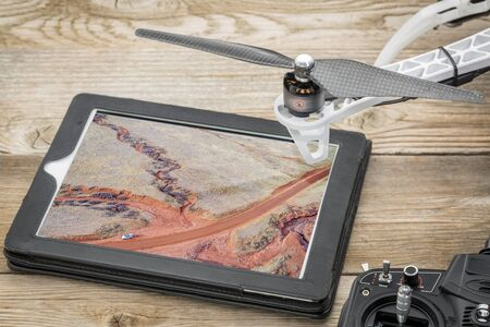 aerial photography concept - reviewing pictures of Colorado foothills with a dry stream on a digital tablet with a drone rotor and radio controller, screen picture copyright by the photographer Stock Photo