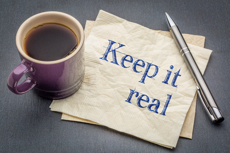 Keep it real text - handwriting on a napkin with a cup of coffee