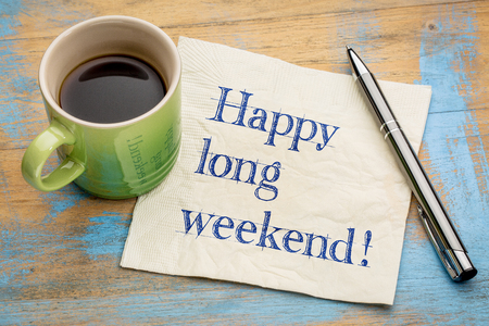 weekend: Happy long weekend  - handwriting on a napkin with a cup of espresso coffee