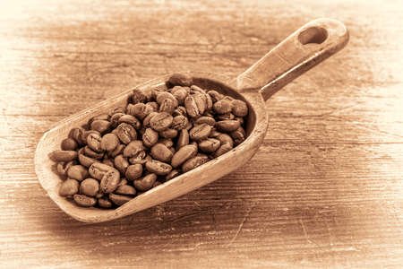 rustic scoop of roasted coffee beans against a grunge painted wood background, retro sepia toning Stock Photo