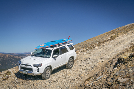 the jeep: LEADVILLE, CO, USA - SEPTEMBER 27, 2016: Toyota 4Runner SUV (2016 Trail edition) with a paddleboard descending  from the Mosquito Pass on a rocky jeep trail in Colorados Rocky Mountains