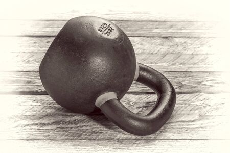 heavy iron kettlebell on a rustic wood background - fitness concept - retro sepia opalotype processing Stock Photo