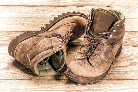 a pair of old, well-worn, hiking boots on weathered wood, retro sepia toning Stock Photo