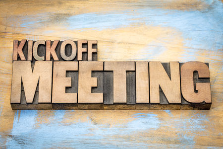 Kickoff meeting word abstract in letterpress wood type printing blocks against grunge wooden surface Archivio Fotografico