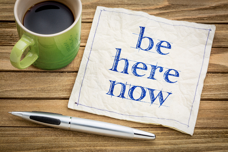 Be here now - motivational handwriting on  a napkin with a cup of coffee