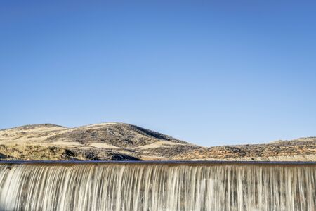 water cascading over a dam in Colorado foothills against blue sky