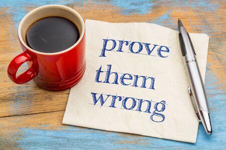 Bewijs het verkeerd van hen - handschrift op een servet met een kopje koffie Stockfoto