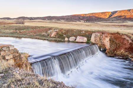 a small dam in northern Colorado foothills - Park Creek is running the water diverted from the North Fork of Poudre River to fill a reservoir downstream