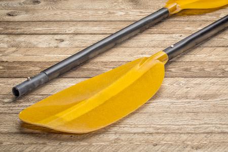 take-apart fiberglass whitewater kayak paddle against weathered wood background