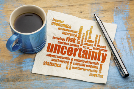 uncertainty and risk word cloud on a napkin with a cup of coffee Banco de Imagens