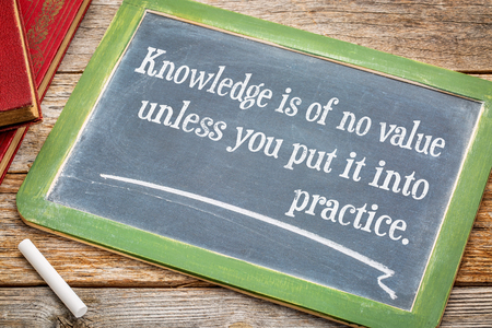 Knowledge is of no values unless you put it into practice - motivational text on a  slate blackboard with chalk and a stack of books against rustic wooden table