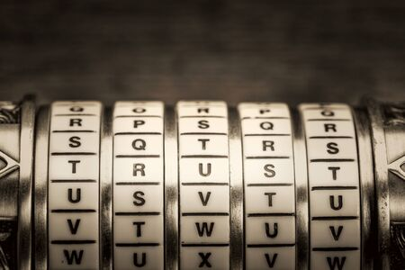 secret code: trust word as a password to combination puzzle box with rings of letters, black and white platinum toned image