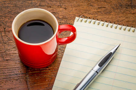 grune: blank paper notepad with a pen and coffee on grunge wooden table