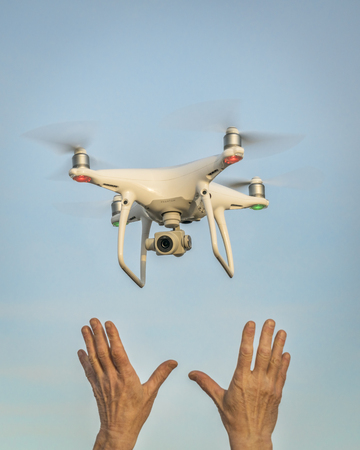 CARR, CO, USA - APRIL 12, 2017:  Launching DJI Phantom 4 pro quadcopter drone - operator hands and drone against sky. Editorial