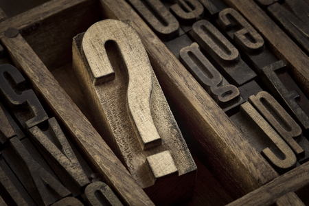 typesetter: question mark - vintage wooden letterpress type block in old typesetter drawer among other letters, sepia toned black and white image