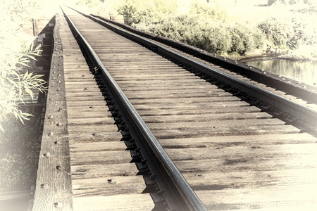 railroad tracks on a trestle crossing a river - travel concept, retro hand tinted opalotype processing Stock fotó