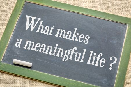 What makes a meaningful life? A question on a slate blackboard with a white chalk against burlap canvas
