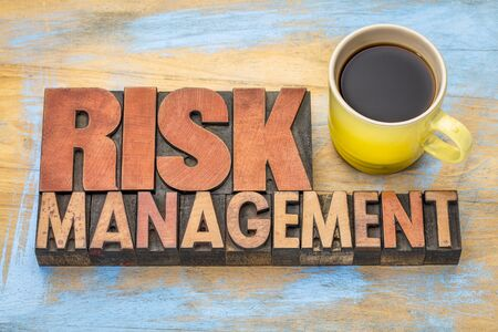 risk management banner in vintage letterpress wood type blocks with a cup of coffee