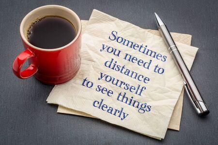 때로는 물건을 분명히보기 위해 거리를 두어야합니다 - 회색 슬레이트 돌 배경에 커피 한잔과 함께 냅킨에 필기