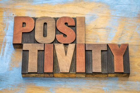 positivity word abstract in in vintage letterpress wood type Banco de Imagens