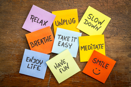 take it easy: relax, unplug, slow down, breathe, take it easy, meditate,enjoy life, have and smile motivational lifestyle reminders on colorful sticky notes against grunge wood