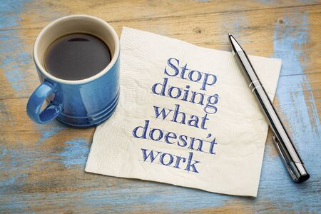 stop doing what does not work  advice or reminder - handwriting on a napkin with a cup of coffee