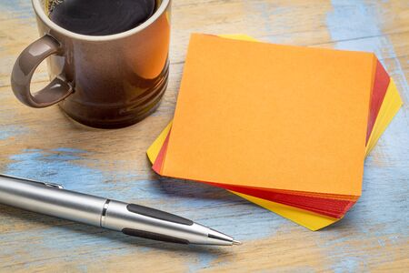 blank spaces: blank orange sticky note with a pen and a cup of coffee