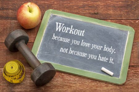 Workout because you love your body, not because you hate it  -  fitness concept on a slate blackboard against weathered red painted barn wood with a dumbbell, apple and tape measure Imagens