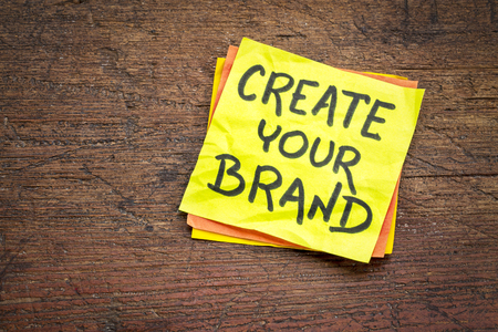 Create your brand - advice or reminder on a sticky note against rustic wood board Фото со стока