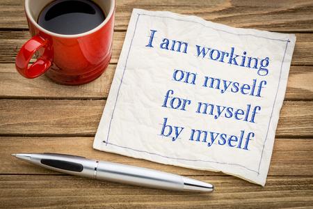 나는 혼자서 일하고있다. 혼자서 - 커피 한잔과 함께 냅킨에 필체 쓰기. 스톡 콘텐츠