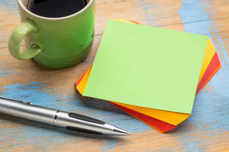 blank spaces: blank green sticky note with a pen and a cup of coffee