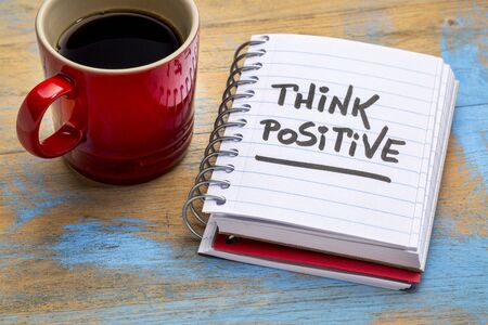 think positive - inspirational handwriting in a notebook with a cup of coffee