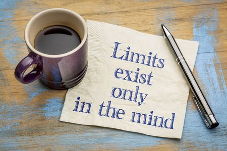 exist: Limits exist only in the mind  - inspirational handwriting on a napkin with a cup of espresso coffee Stock Photo