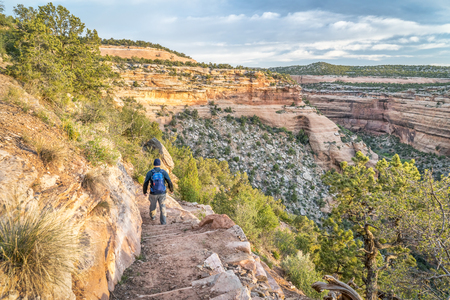 Male hiker descending on a steep trail into Ute Canyon in Colorado National Monument, morning spring scenery photo