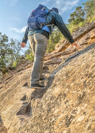 Male hiker climbing a steep trail of Ute Canyon in Colorado National Monument, morning spring scenery photo