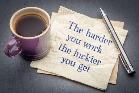 あなたが働くより、あなたが得る幸運 - 灰色のスレート石の背景に対してコーヒーのカップとナプキンにインスピレーション手書き